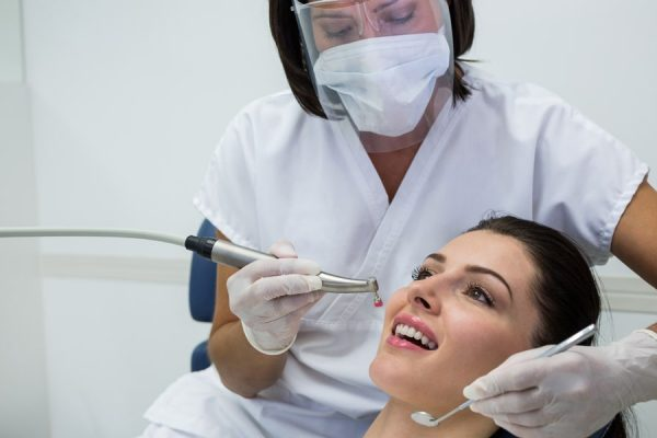 dentist-examining-female-patient-with-tools-min